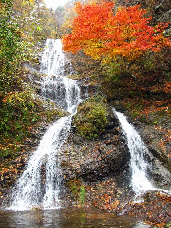 Nakasendo Way Karasawa waterfall with red maple leaves autumn